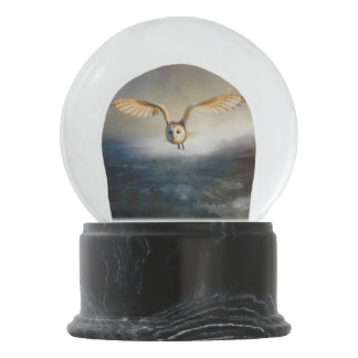 An barn owl flies over the lake snow globe