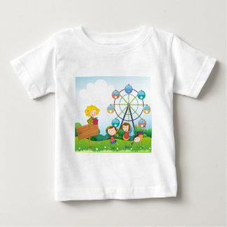 An empty signboard with kids near a ferris wheel tee shirts