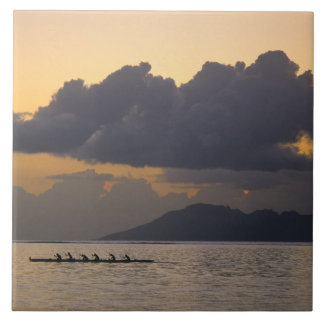 An outrigger canoe team practices off the coast large square tile
