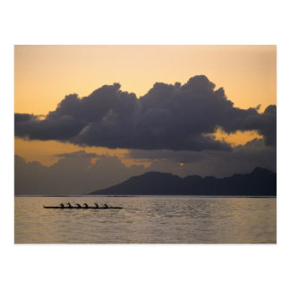 An outrigger canoe team practices off the coast postcard