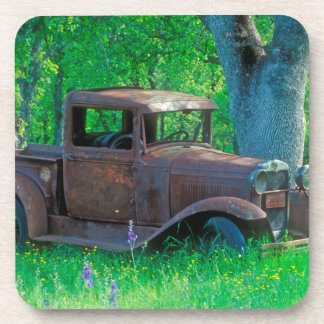 Antique rusted truck in a meadow coaster