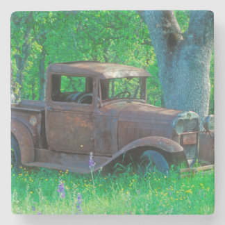Antique rusted truck in a meadow stone coaster