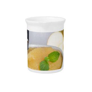 Applesauce with cinnamon in stoneware bowl beverage pitcher