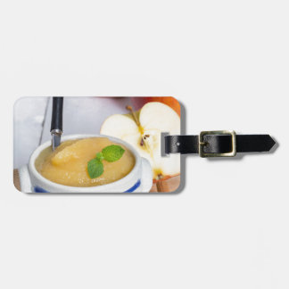 Applesauce with cinnamon in stoneware bowl luggage tags