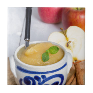 Applesauce with cinnamon in stoneware bowl small square tile