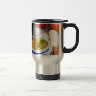 Applesauce with cinnamon in stoneware bowl stainless steel travel mug