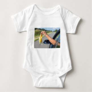 Arm dropping peel of banana out car window baby bodysuit