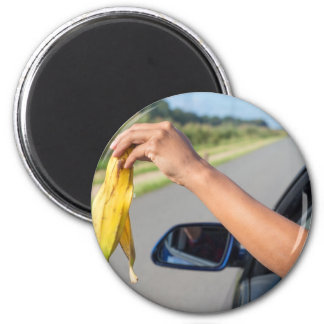 Arm dropping peel of banana out car window magnet