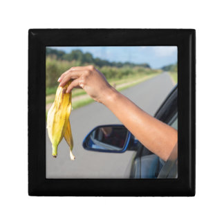 Arm dropping peel of banana out car window small square gift box