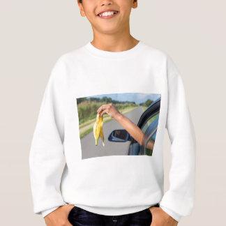 Arm dropping peel of banana out car window sweatshirt