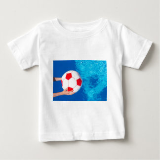 Arms holding beach ball above swimming pool water baby T-Shirt