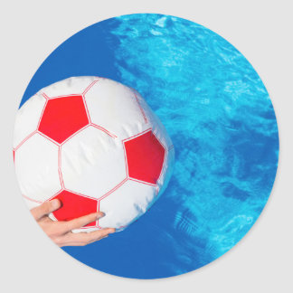 Arms holding beach ball above swimming pool water classic round sticker