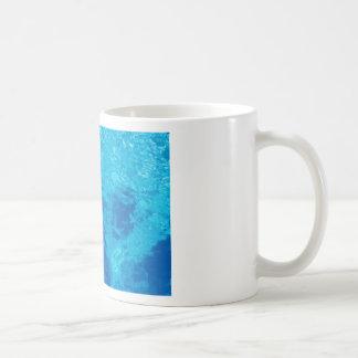 Arms holding beach ball above swimming pool water coffee mug