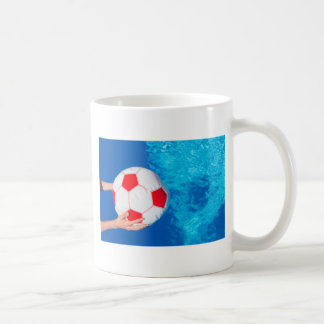 Arms holding beach ball above swimming pool water coffee mug