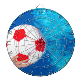 Arms holding beach ball above swimming pool water dartboard