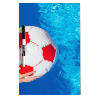 Arms holding beach ball above swimming pool water dry erase board