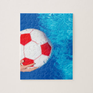 Arms holding beach ball above swimming pool water jigsaw puzzle