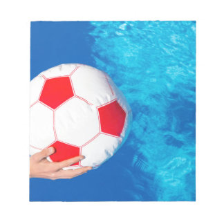 Arms holding beach ball above swimming pool water notepad