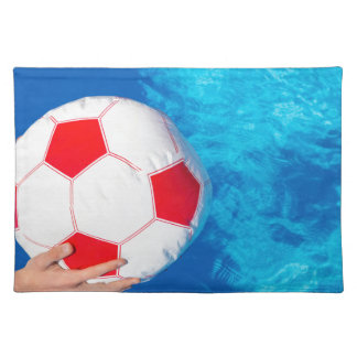 Arms holding beach ball above swimming pool water placemat