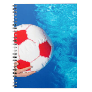 Arms holding beach ball above swimming pool water spiral notebook