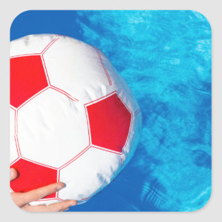 Arms holding beach ball above swimming pool water square sticker