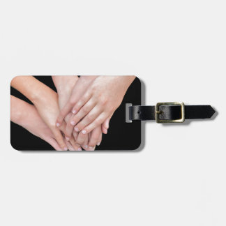 Arms of girls with hands over each other luggage tag
