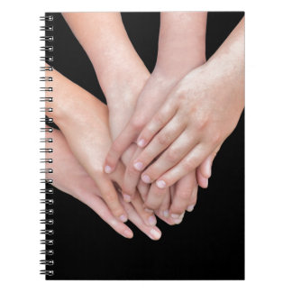 Arms of girls with hands over each other notebooks