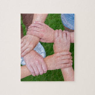 Arms with hands of children holding together jigsaw puzzle