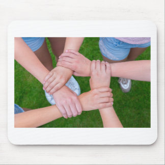 Arms with hands of children holding together mouse pad