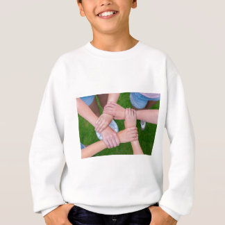 Arms with hands of children holding together sweatshirt