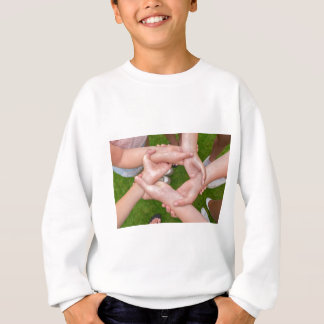 Arms with hands of girls holding each other sweatshirt