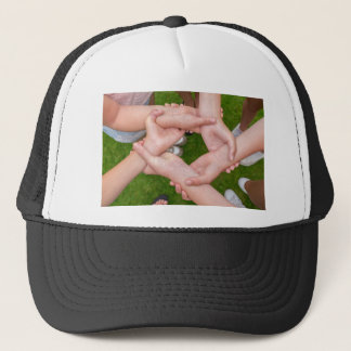 Arms with hands of girls holding each other trucker hat
