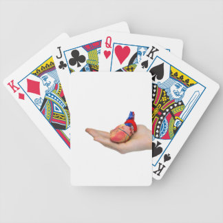 Artificial human heart model on hand bicycle playing cards