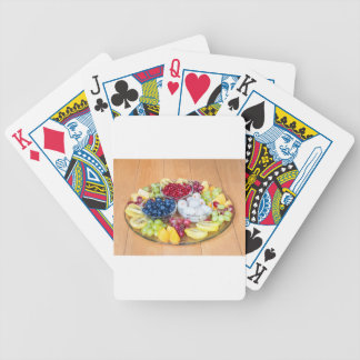 Assortment fresh summer fruit on glass scale bicycle playing cards