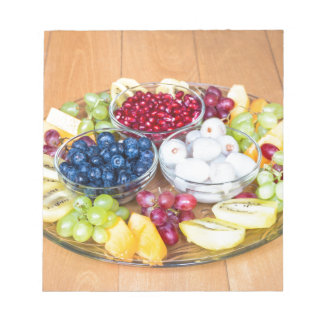 Assortment fresh summer fruit on glass scale notepad