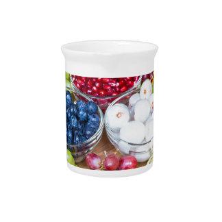 Assortment fresh summer fruit on glass scale pitcher