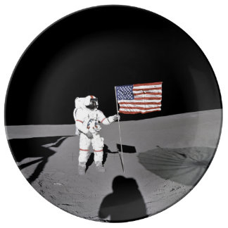 Astronaut stands by the U.S. flag on Moon Plate