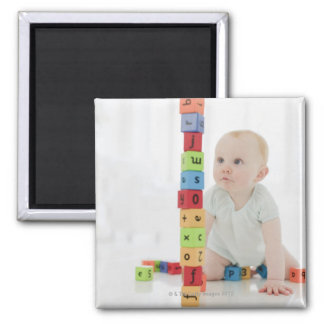 Baby on floor looking at stacked wood blocks square magnet