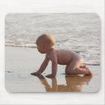 Baby playing in the sand on the beach mouse pads