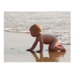 Baby playing in the sand on the beach postcard