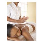 Back massage. Woman receiving a back massage by Postcard