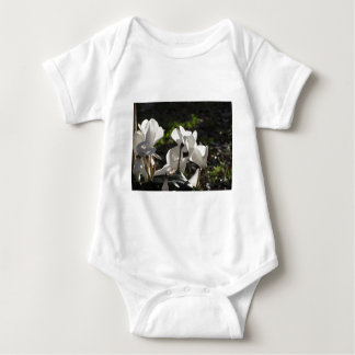 Backlits white cyclamen flowers on dark background baby bodysuit