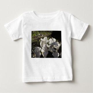 Backlits white cyclamen flowers on dark background baby T-Shirt