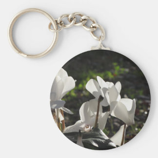 Backlits white cyclamen flowers on dark background key ring