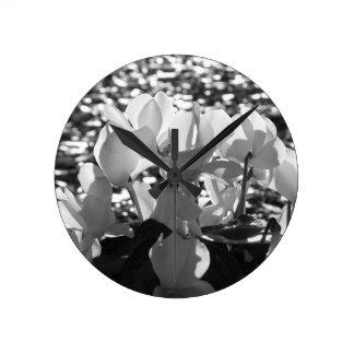 Backlits white cyclamen flowers on dark background round clock