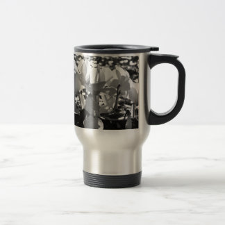 Backlits white cyclamen flowers on dark background travel mug