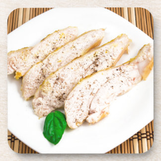 Baked chicken breast sliced on a white plate beverage coaster