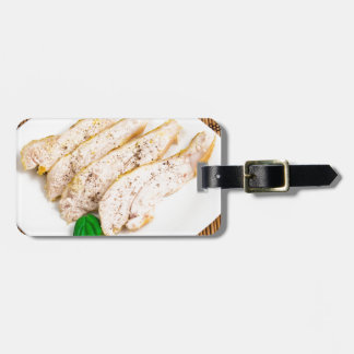 Baked chicken breast sliced on a white plate luggage tag