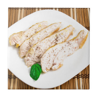 Baked chicken breast sliced on a white plate small square tile