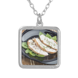 Baked slices of chicken meat on a black plate silver plated necklace